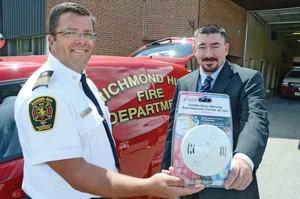 Steve Kraft (سمت چپ)، رئیس آتش نشانی شهر ریچموندهیل در حال دریافت کردن یکی از ۳۳۰ هشدار دهنده دود آتش.
