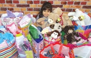 ساشا در کنار هدایای تولد 6 سالگی خود که به کودکان نیازمند هدیه کرده است