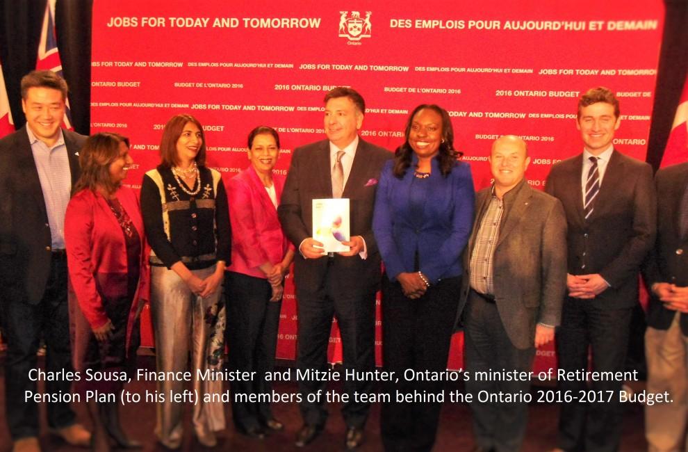 چارلز سوزا وزیر دارایی و میتزی هانتر(سمت چپ او) وزیر و مسئول طرح بیمه بازنشتگی انتاریو و تیم شرکت کننده در تنظیم بودجه پس از جلسه معرفی برنامه بودجه امسال و پرسش و پاسخ با خبرنگاران رسانه های قومی در ۲۶ فوریه