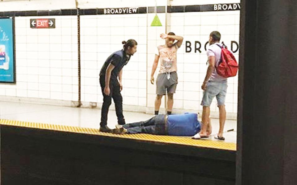 این عکس توسط یکی از شاهدان در صحنه گرفته شده  ـ تصویر سه مردی که با همدیگر  این شخص نابینا را از روی ریلهای مترو نجات دادند.